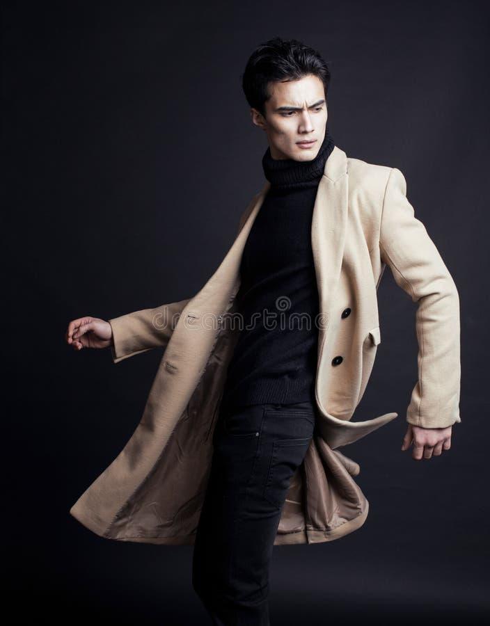 Chłodno istny młody człowiek w żakiecie na czarny tła pozować fotografia stock