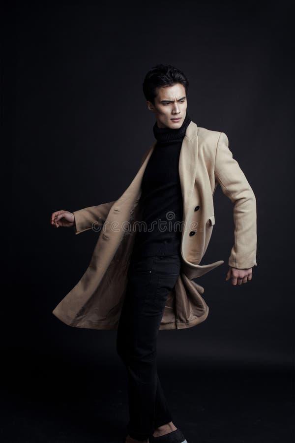 Chłodno istny młody człowiek w żakiecie na czarnym tle obraz stock