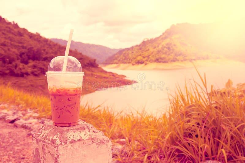 Chłodno kawa w plastikowych filiżankach z tło widokami jako rezerwuary, obrazy stock