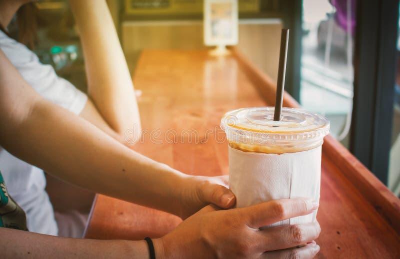 Chłodno kawowy kubek w kobiety ` s rękach na drewnianym stole przy sklep z kawą zdjęcie royalty free