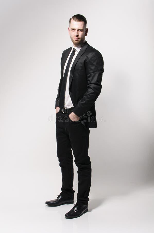 Chłodno młody człowiek w ciemnym kostiumu fotografia stock