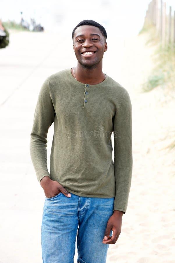 Chłodno młody czarnego faceta ono uśmiecha się outside z ręką w kieszeni zdjęcie stock