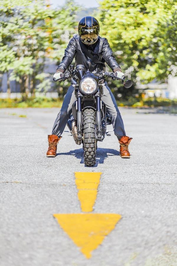 Chłodno przyglądający motocyklu jeździec na na zamówienie scrambler stylu caf zdjęcie stock