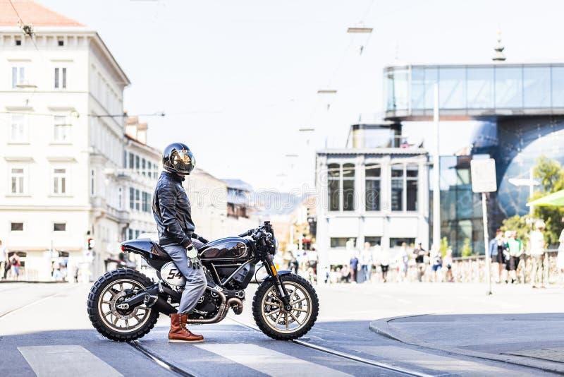 Chłodno przyglądający motocyklu jeździec na na zamówienie scrambler stylu kawiarni setkarzie fotografia stock