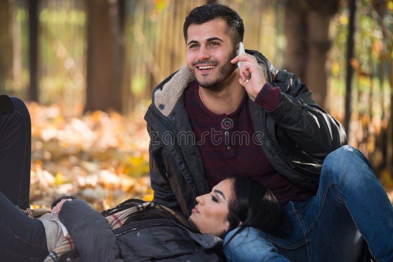 Chłopak Opowiada Na telefonie Podczas gdy Cieszący się jesień parka obraz stock