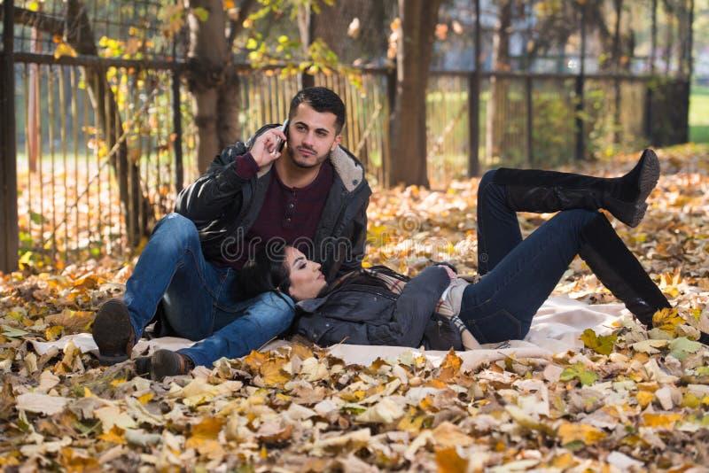 Chłopak Opowiada Na telefonie Podczas gdy Cieszący się jesień parka obrazy royalty free