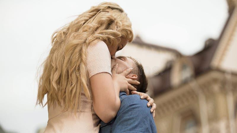 Chłopak podnosi jego dziewczyny up i całuje ona, namiętny związek zdjęcie stock
