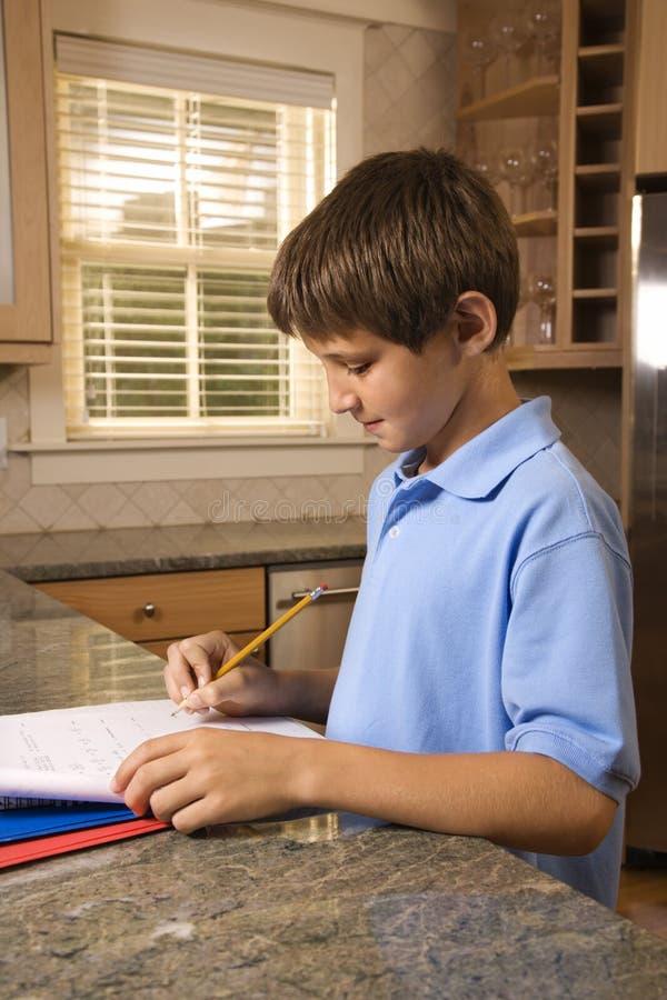 chłopak robi odpierająca pracy domowej kuchni obraz stock