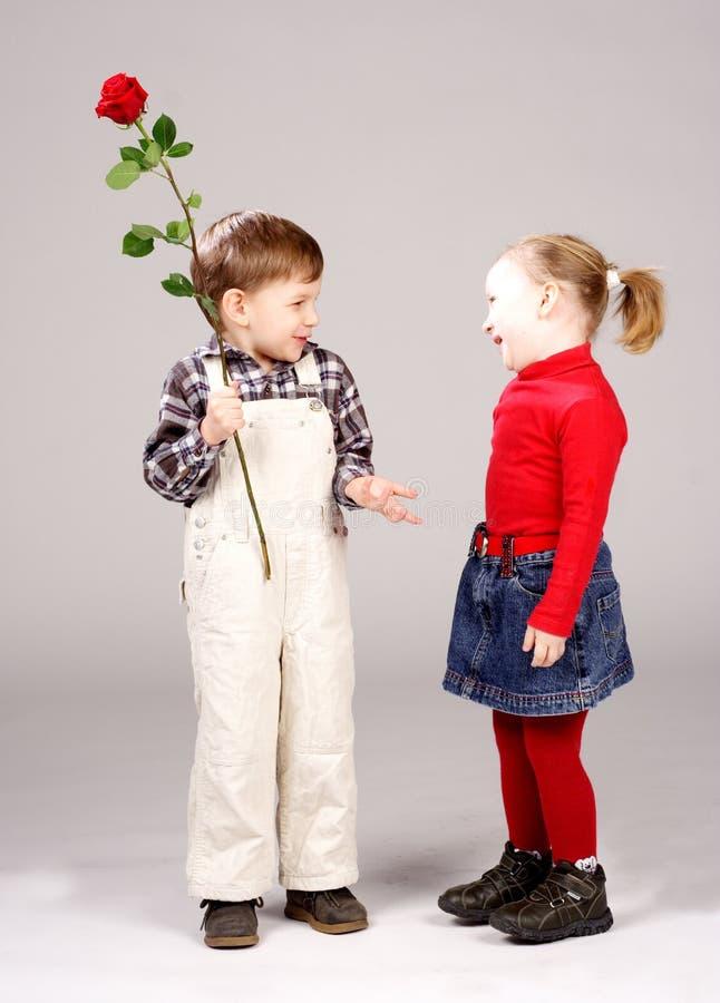 chłopcy dziewczyna daje wzrosła do przedszkola zdjęcie royalty free