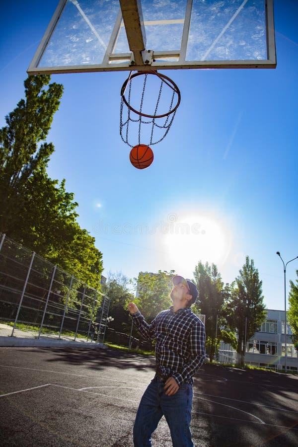Chłopcy grający w koszykówkę na zewnątrz na boisku sportowym obraz royalty free