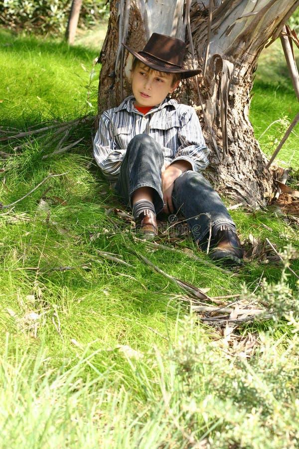 chłopcy gumową siedząc drzewo obraz stock