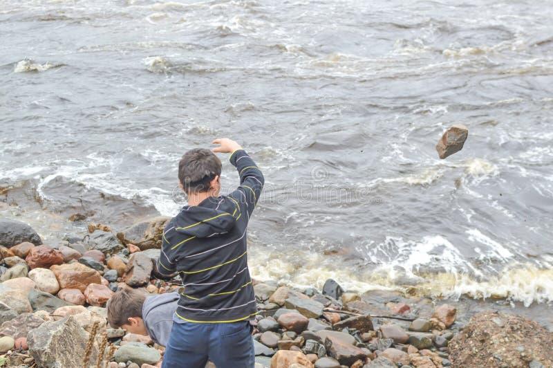 Chłopcy rzucają kamieniami w rzekę zdjęcia royalty free
