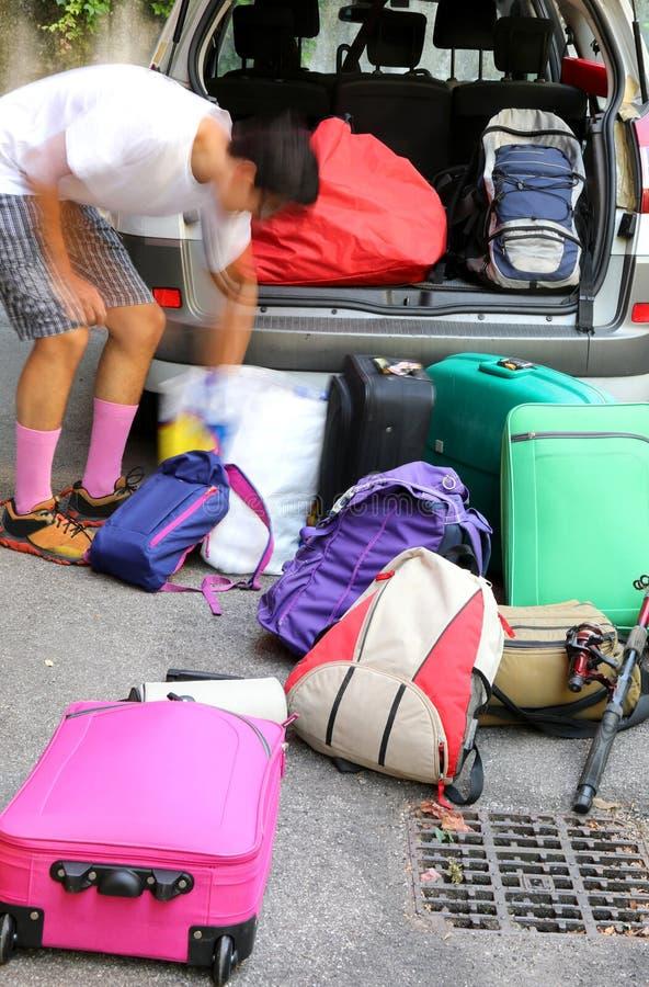 Chłopiec ładuje bagaż dla wakacje w samochodzie fotografia stock