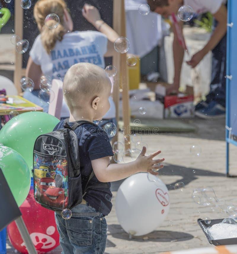 Chłopiec łapie mydlanych bąble na wakacje obraz royalty free