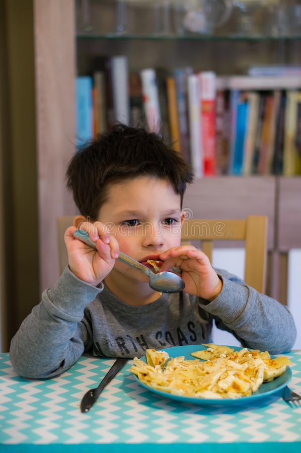 Chłopiec łasowania bliny zdjęcie royalty free
