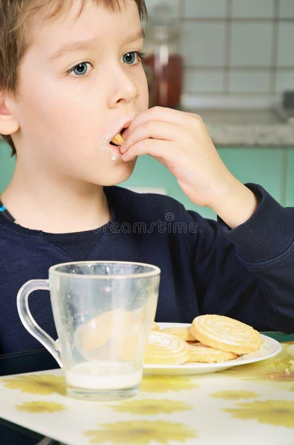 Chłopiec łasowania ciastka, siedzi przy obiadowym stołem pionowo zdjęcia royalty free