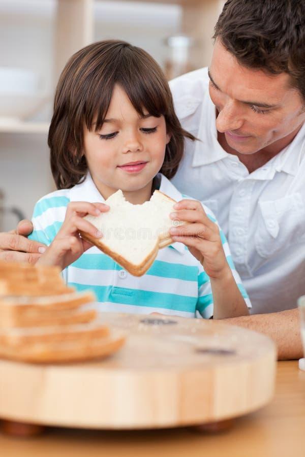 chłopiec łasowania ojciec jego mała kanapka zdjęcia royalty free