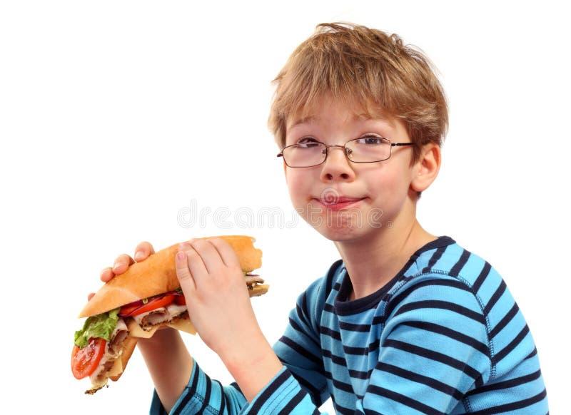 Chłopiec łasowania wielka kanapka obrazy royalty free
