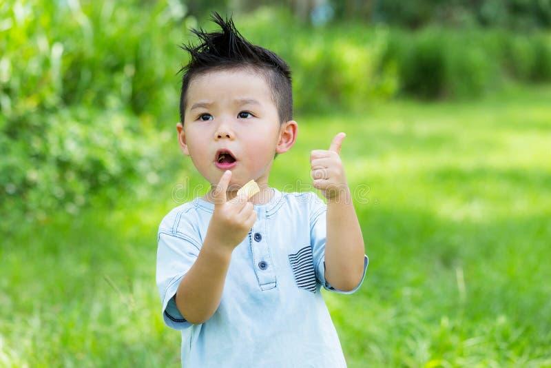 Chłopiec łasowanie z przekąską up i seansu kciukiem obrazy stock