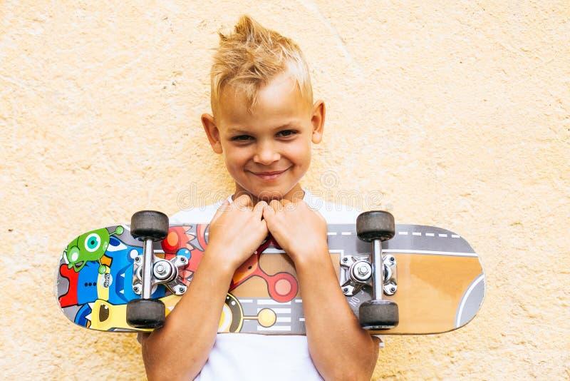 Chłopiec łyżwiarka pozuje z deskorolka zdjęcie royalty free
