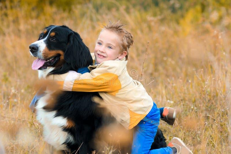 chłopiec ściska jego psa na spacerze przez jesieni w żółtej kurtce fotografia stock
