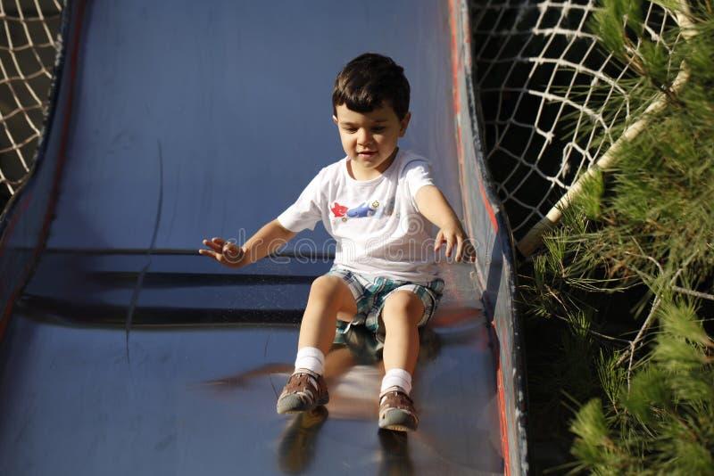 Chłopiec ślizga się w dół plenerowego obruszenie zdjęcia stock