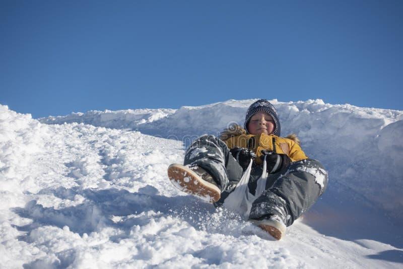 Chłopiec ślizga się w dół wzgórze w śniegu w zimie zdjęcia stock