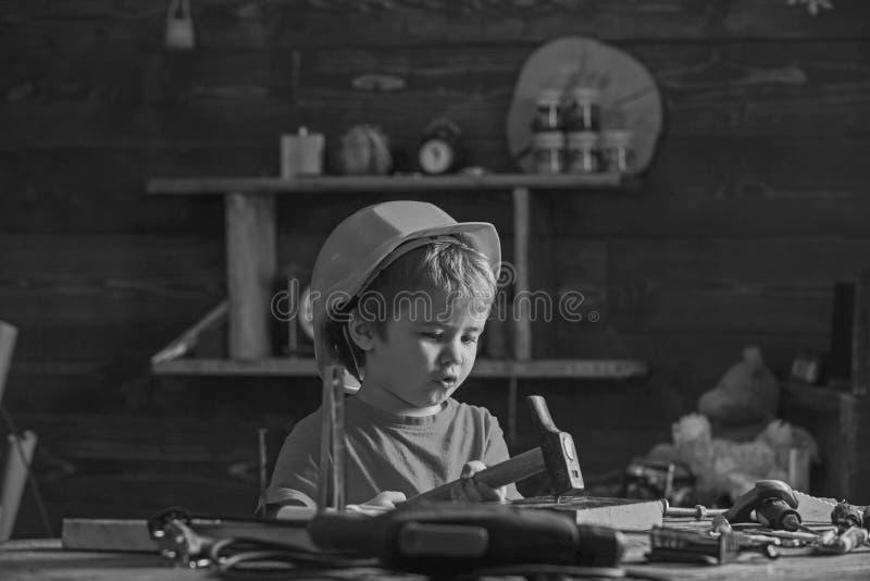 Chłopiec śpiewacka piosenka podczas gdy młotkujący gwóźdź w drewnianego blok Mały dzieciaka obsiadanie przy pracującym stołem w w zdjęcie royalty free