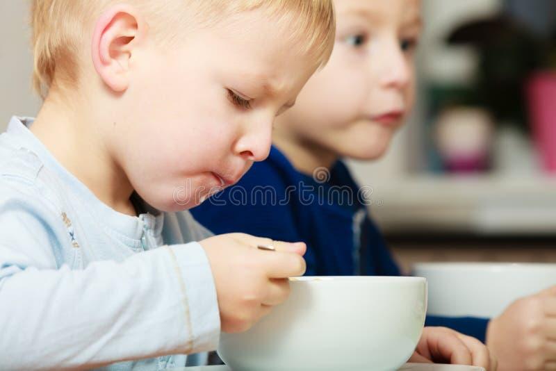 Chłopiec żartują dzieci je kukurydzanych płatków śniadaniowego posiłek przy stołem obraz stock