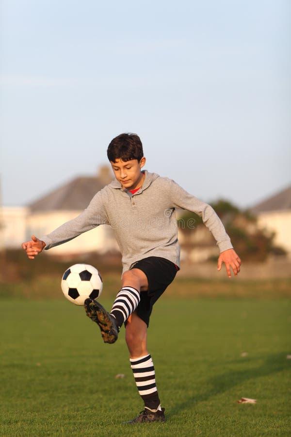 Chłopiec żonglerki z piłki nożnej piłką outside obraz royalty free