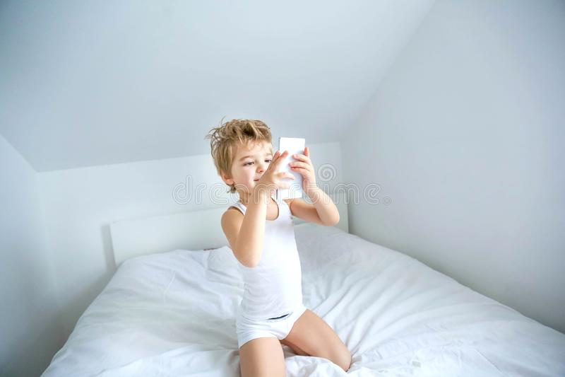 Chłopiec bawiący się na elektronicznym tablecie w swojej sypialni Społeczny problem komunikacji dzieci we współczesnym świecie zdjęcia stock