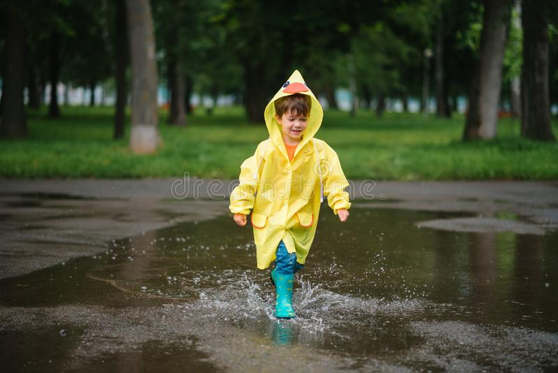 Chłopiec bawiący się w deszczowym letnim parku Dziecko z parasolem, wodoszczelnym płaszczem i butami skaczącymi w kałuży i błocie zdjęcia royalty free