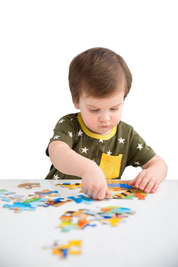 Chłopiec bawić się łamigłówkę na białym tle zdjęcia stock