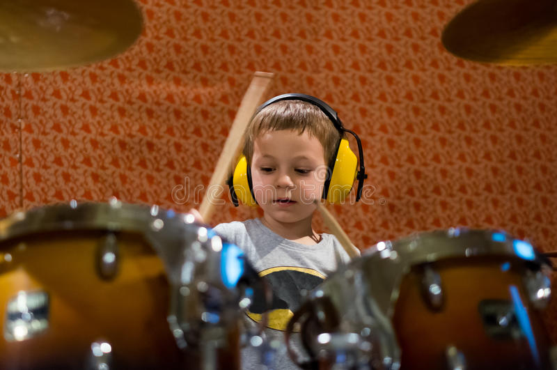 Chłopiec bawić się bębeny z ochrona hełmofonami obraz royalty free