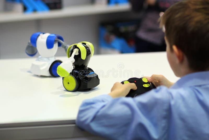 Chłopiec bawić się batalistycznych walczących roboty z pilotem do tv robotyka obraz stock
