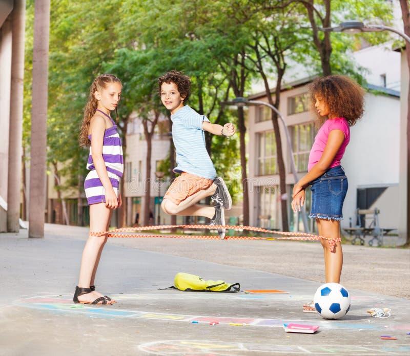 Chłopiec bawić się elastics z przyjaciółmi outside fotografia royalty free