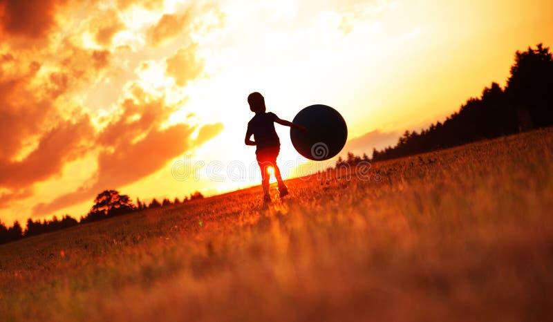 Chłopiec bawić się futbol na łące obraz royalty free