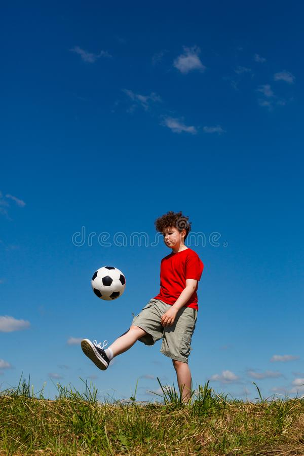 Chłopiec bawić się futbolowy plenerowego obrazy royalty free