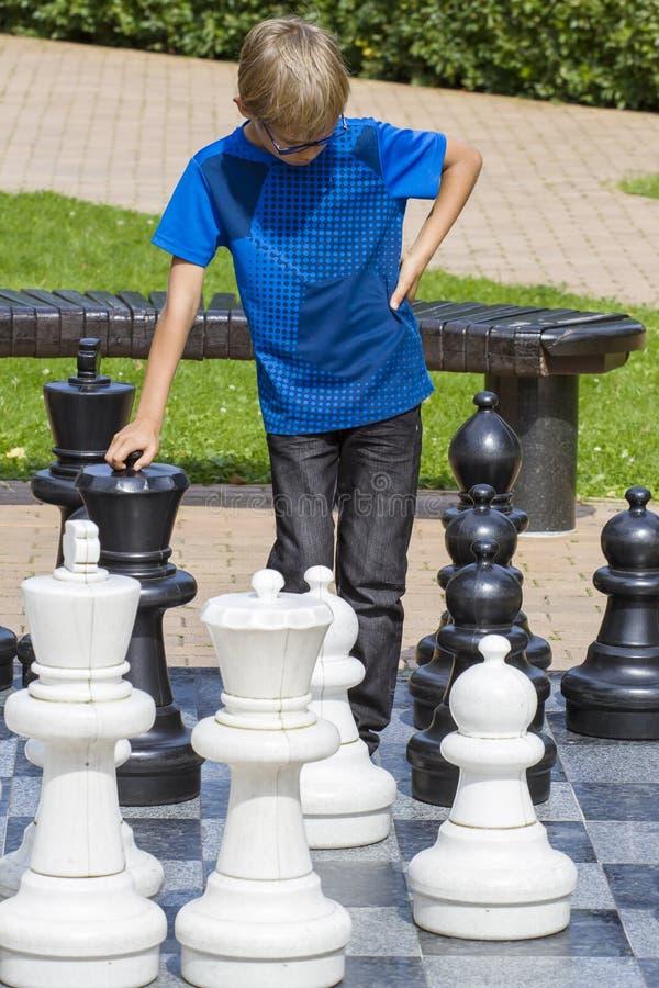 Chłopiec bawić się gigantycznego szachy outdoors w parku Dziecko myśleć strategicznie o jego kolejnym kroku fotografia stock