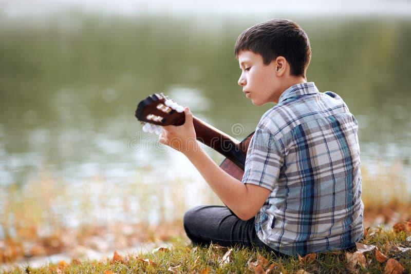 Chłopiec bawić się gitarę akustyczną, siedzi na banku rzeka, jesień las, piękna natura i odbicie t, przy zmierzchem, zdjęcie royalty free