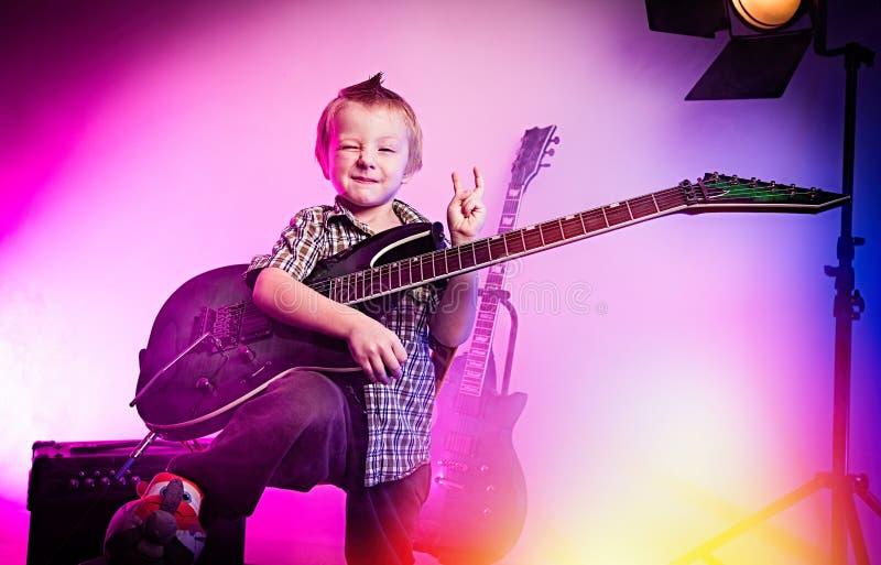 Chłopiec bawić się gitarę, dzieciaka gitarzysta zdjęcia royalty free