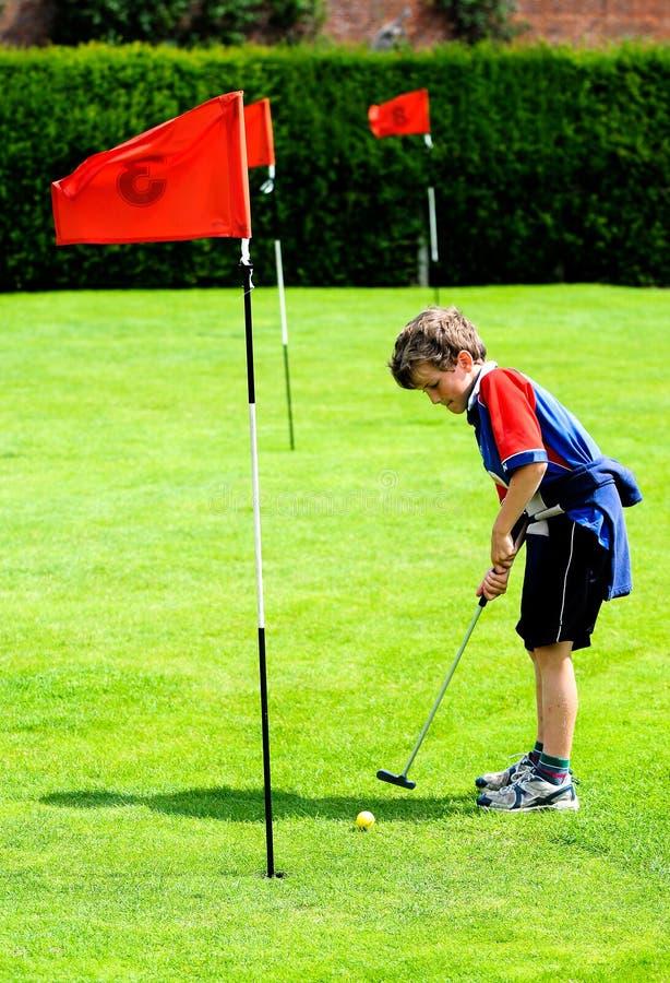 chłopiec bawić się golfowy mini obraz stock