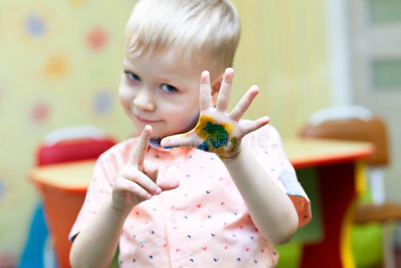 Chłopiec bawić się i jego ręki zakrywający z jaskrawymi kolorami obrazy stock