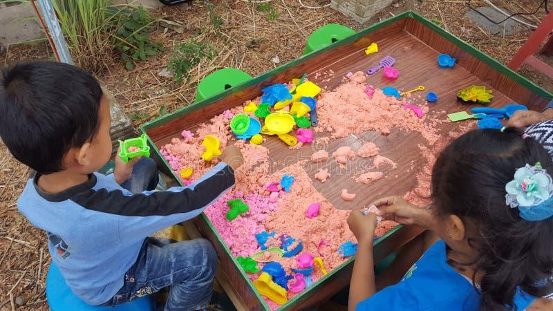 Chłopiec bawić się kolorowego piasek zdjęcia stock