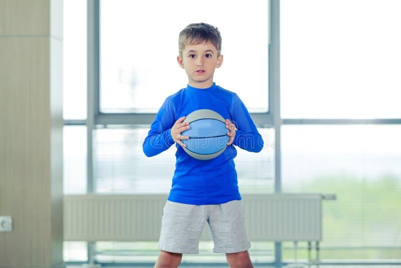 Chłopiec bawić się koszykówki błękitną formę i piłkę obraz royalty free