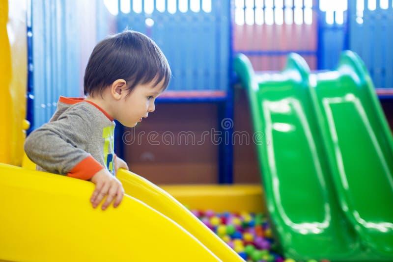 Chłopiec bawić się na boisku w dziecka ` s labiryncie, Dziecka ` s obruszenie fotografia royalty free