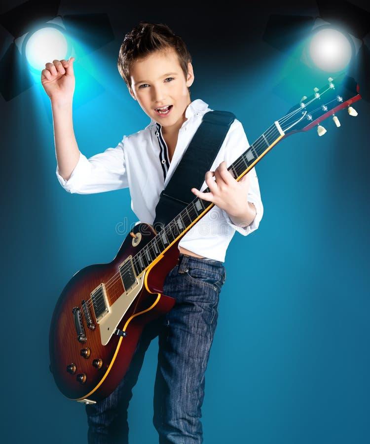 Chłopiec bawić się na gitarze elektrycznej na scenie zdjęcia royalty free