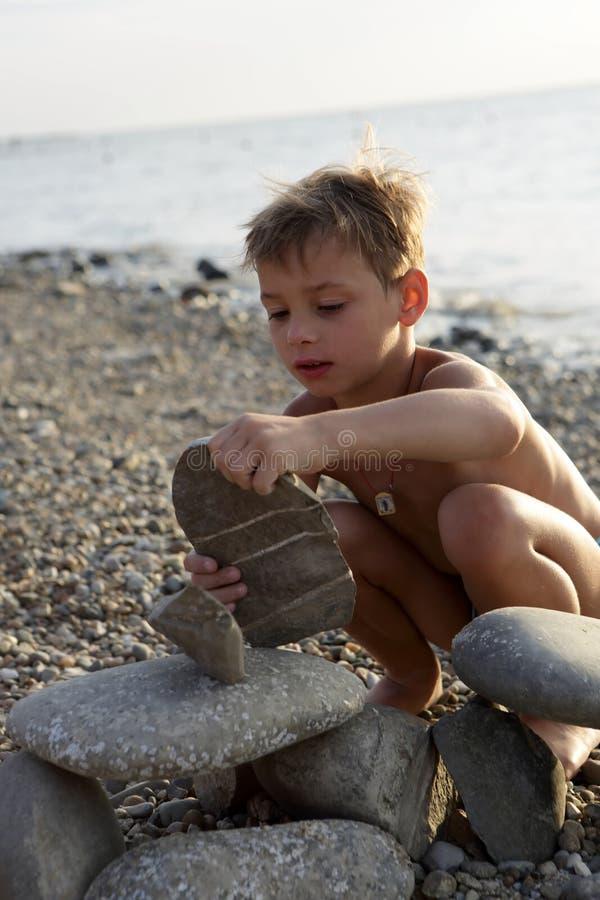 Chłopiec bawić się na otoczak plaży zdjęcia stock