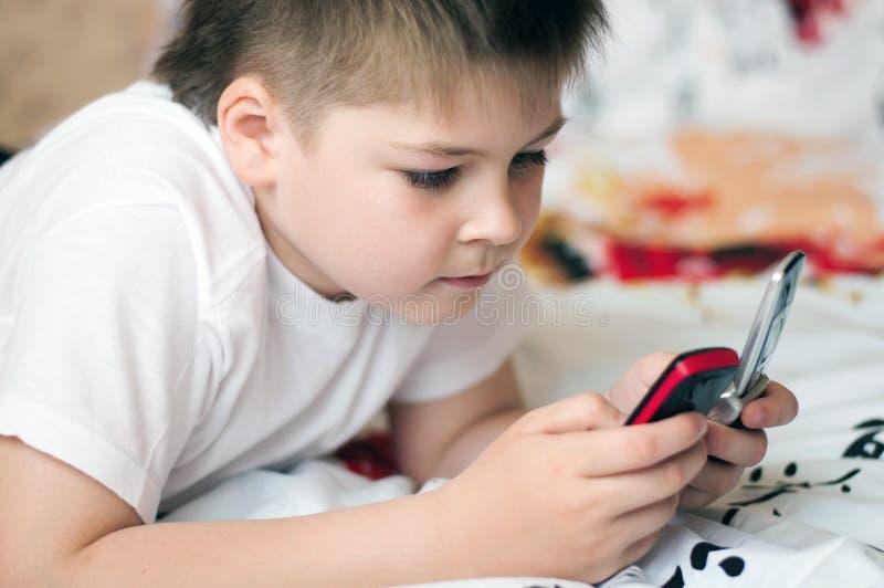 Chłopiec bawić się na telefon komórkowy obrazy royalty free
