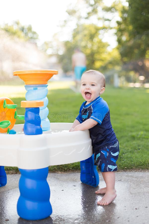 Chłopiec bawić się outside w wodnym stole obraz royalty free